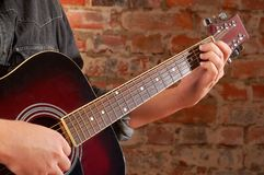 Playing on acoustic guitar Stock Image