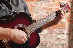 Playing on acoustic guitar Royalty Free Stock Images