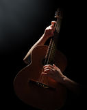 Playing on acoustic guitar. On a black background Stock Images