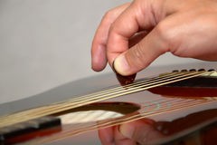 Playing acoustic guitar: hand with pick on strings. Educational or tutorial illustration of guitarist hand with pick playing classic acoustic guitar Royalty Free Stock Images