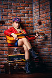 Playing acoustic guitar. Modern child girl playing guitar and singing a song. Rock star, rock music, pop music concept Stock Images