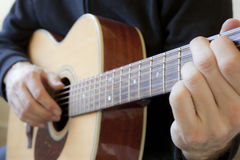 Playing an acoustic guitar. A person learning to play the acoustic guitar Royalty Free Stock Images