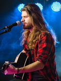 Playing acoustic guitar and singing on stage Royalty Free Stock Photography