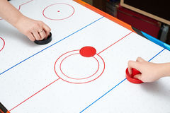 Playing on air hockey Stock Images