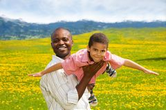 Playing airplane. Black father playing with little boy holding him in airplane pose in spring yellow dandelion field Stock Image