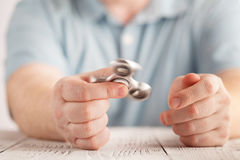 Playing with aluminium fidget spinner. Stress relieving toy Royalty Free Stock Photo