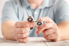 Playing with aluminium fidget spinner. Stress relieving toy Stock Photo