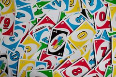Playing american card game Uno, holding game cards in female hand. Deck of Uno game cards scattered all over on a table. American stock images