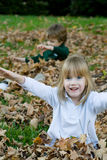 Playing in the autumn leaves. A set of boy girl twins playing in the autumn leaves Stock Image