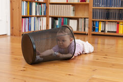 Playing baby. Baby lying on the ground playing with a waste paper basket Royalty Free Stock Images