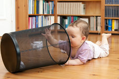 Playing baby. Baby lying on the ground playing with a waste paper basket Royalty Free Stock Photography
