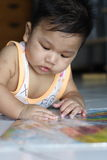Playing Baby. A young toddler playing with a sheet of paper Stock Photo