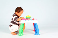 Playing baby. An Unhappy Asian toddler playing with his toy alone Royalty Free Stock Images