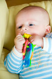 Playing baby. Baby playing with toy and lying on sofa royalty free stock photography