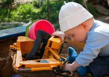 Playing baby. Little boy playing in a sand pit with toys Stock Photo