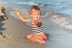 Playing baby girl on a sand beach Stock Images
