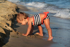 Playing baby girl on a sand beach Royalty Free Stock Image