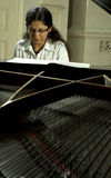 Playing The Baby Grand. Portrait of a female piano teacher looking downward as she plays baby grand piano.  Taken from across open piano top Royalty Free Stock Photos