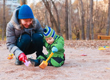 Playing with baby outdoors. Teaching child to dig while walking  outdoors in autumn Stock Photos