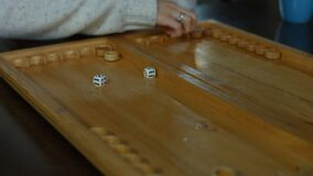 Playing backgammon on a wooden table with dice stock video