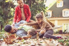 Playing at backyard at autumn season is fun. Happy family. Stock Photography