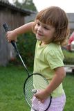 Playing badminton. Little, cute girl playing badminton outdoors on a summer day Royalty Free Stock Photos