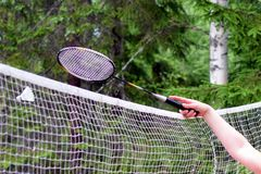 Playing badminton outdoors. Close up of hand, racket and net Stock Photos