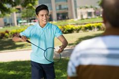 Playing badminton. Vietnamese teenager playing badminton in the park Royalty Free Stock Photo
