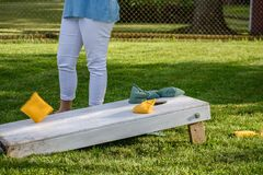 Playing bags game in backyard. Lower body only of young woman standing by corn hole board on sunny day royalty free stock image