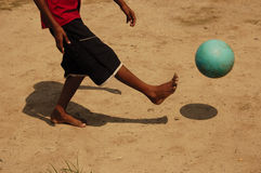 Playing ball. Kid kicking a ball, in a sand field Stock Photography