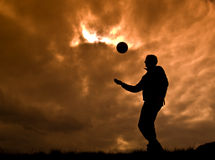 Playing ball. Silhouette man playing on cloudy orange sunset royalty free stock images