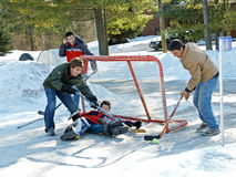 Playing Ball Hockey. A father and sons play ball hockey in the driveway on a sunny winter day in Canada Royalty Free Stock Photography