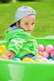 Playing with balls. Cute boy sitting outdoors in the pool with balls stock photos