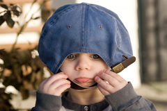 Playing with baseball hat. A portrait of cute young boy wearing adult baseball cap back to front Royalty Free Stock Photography