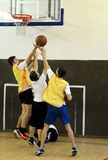 Playing basketball in gym class. Stock Photo
