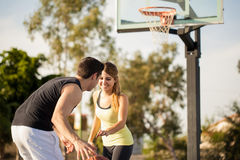 Playing basketball and having fun. Pretty girl having some fun on her first date playing basketball outdoors stock photography