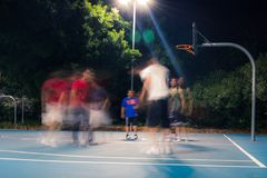 Playing basketball in Sydney with good mates. Basketball game low motion Sydney with good mates at night Stock Photo