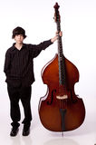 Playing bass. Young boy playing upright bass and smiling royalty free stock photography