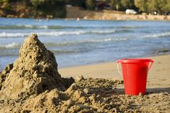 Playing at the Beach. Red bucket and a pyramid made of sand. Mediterranean seashore in the background. Beach located in Northern part of the Crete Stock Photos