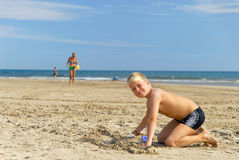 Playing on the beach 4. Young boy is building a sand castle stock images