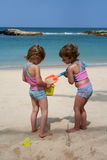 Playing in the Beach. Two little girls play in the sand at a beach in Hawaii Stock Photo