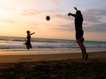 Playing at the beach. Two young people playing at the beach on the sunset Stock Photos