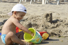 Baby boy playing with beach toys Stock Photos