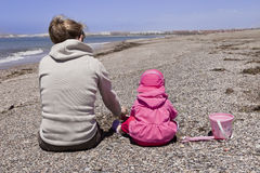 Playing on the beach. A mother and her little daughter, spending time together with beach toys on a rocky beach during a cool but sunny day. The picture was Stock Image