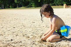 Playing on the sand. Small boy playing in the sand on a lakeside beach Royalty Free Stock Photo