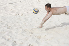 Playing Beach Volleyball. A man dives for the ball while playing beach volleyball on a sandy white beach stock images
