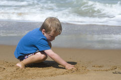 Playing on the beach. Young boy playing in the sand at the beach Royalty Free Stock Images