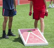 Playing bean bag toss corn hole on turf field. Two boys play corn hole during gym class on a green turf field in the sunshine stock photos