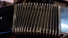 Playing on a big accordion. Playing the harmonica close-up. Old musical instrument Russian bayan - button accordion Royalty Free Stock Photo