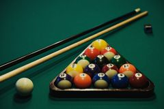 Playing billiard. Billiards balls and cue on green billiards table. Billiard sport concept. Stock Image